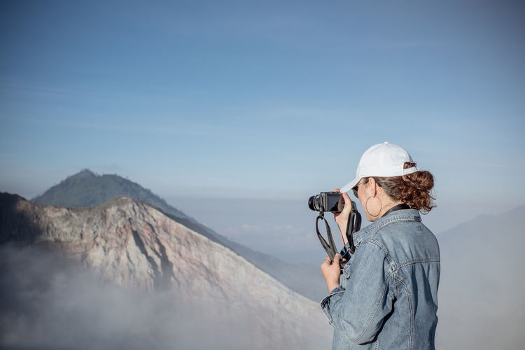 Woman photographing on mountain against sky