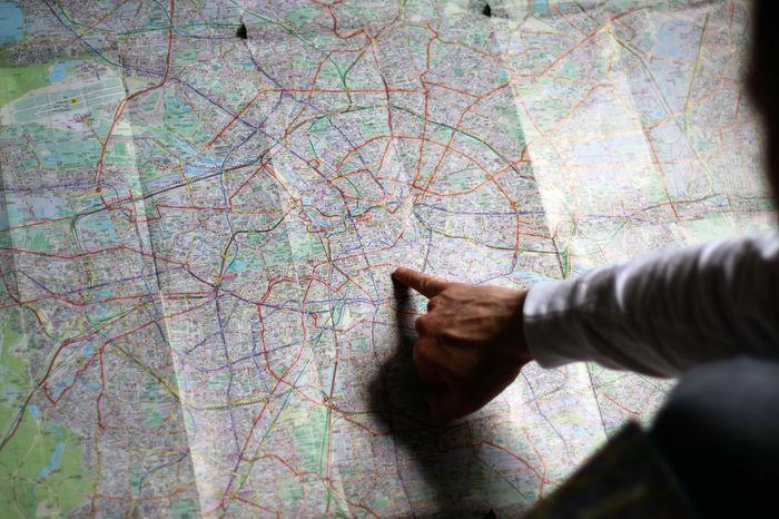 A man using a paper map Berlin Day Finger Footpath Man Map Mapping Orientation Paper Map Person Pointing Pointing Fingers Standing Wayfinder Wayfinding