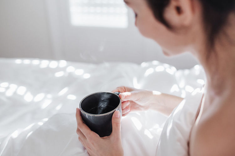 Midsection of woman holding coffee cup on bed