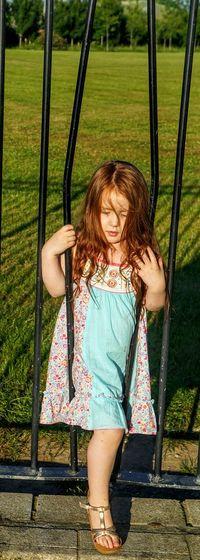 Full length of girl passing through broken gate