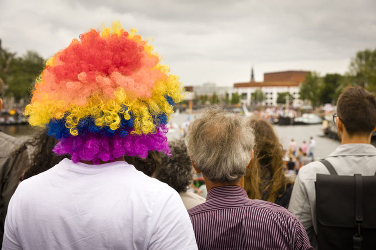 Rear view of man wearing colorful wig