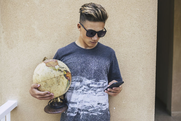 Teenage boy using mobile phone while holding globe against wall