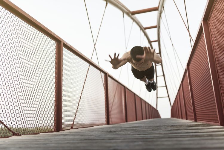 Low angle view of man on footbridge against sky
