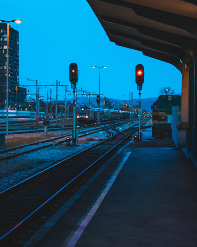 Illuminated railroad station platform against clear sky