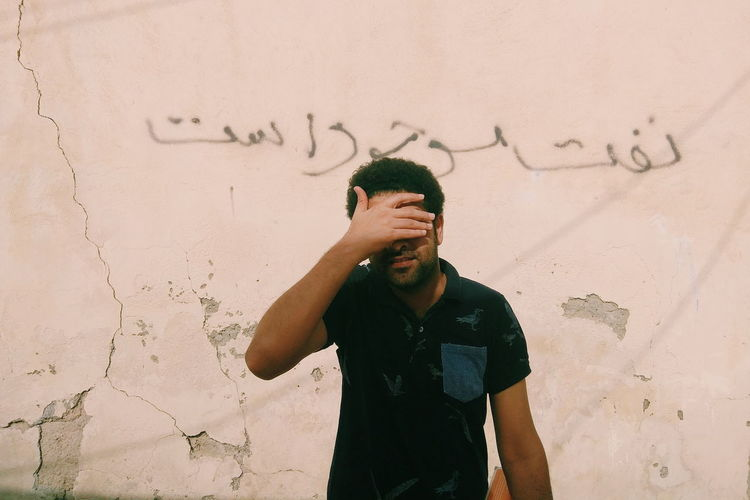 """There is Oil for sell"" this is a wall-note in one of the allies in south of Iran. Next to it stands a local man covering his face. They use oil as an excuse to sell drugs! The Photojournalist - 2018 EyeEm Awards Men Standing Human Hand Written Vandalism"