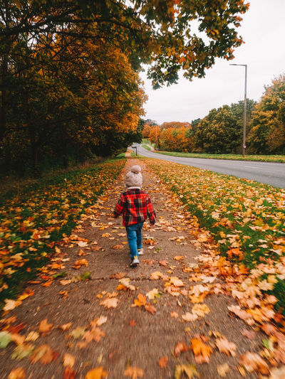 Boy walking on leaves during autumn