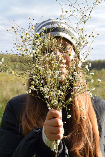Close-up of young woman holding plant in front of park