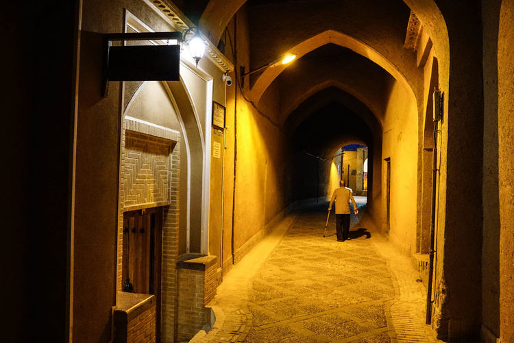 Travel Destinations Travel Photography Iran Shia Community Nomadic Zoroastrian Islamic Architecture Architecture Arch Illuminated Indoors  Real People Building Rear View Built Structure Full Length Corridor One Person Lighting Equipment Arcade Standing Lifestyles Walking Women Adult