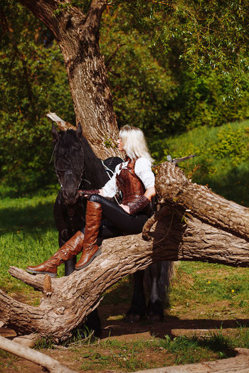 Young Woman In Fairy Costume Sitting On Fallen Tree