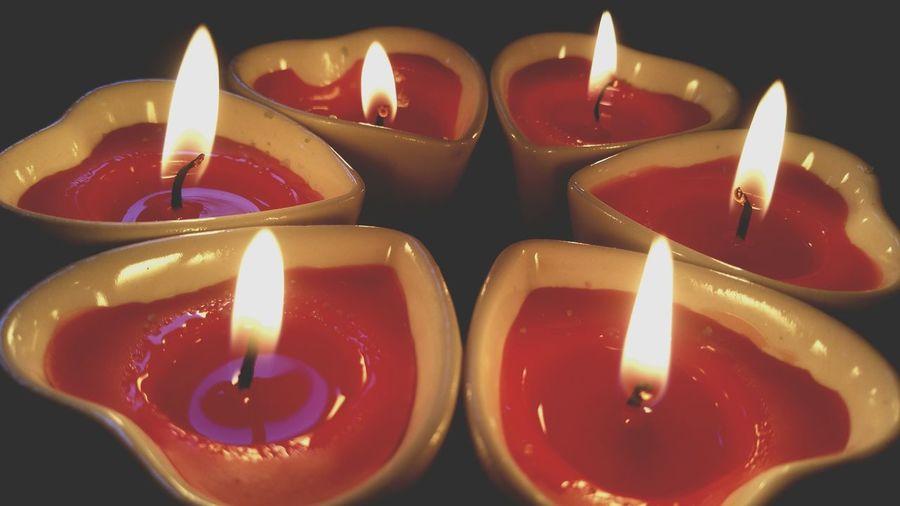 Close-up of heart shape tea light candles burning against black background