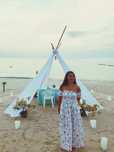 Woman standing against decoration at beach