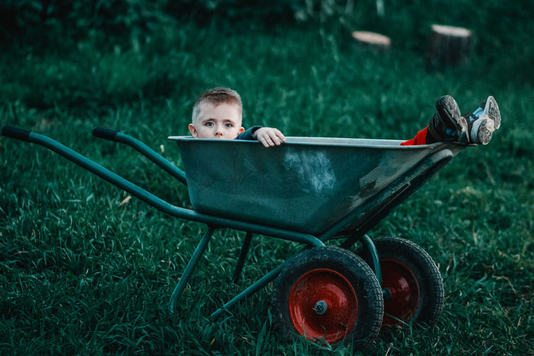 Portrait Of Boy Sitting In Wheelbarrow On Field
