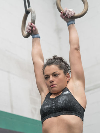 Woman exercising on gymnastic rings at gym