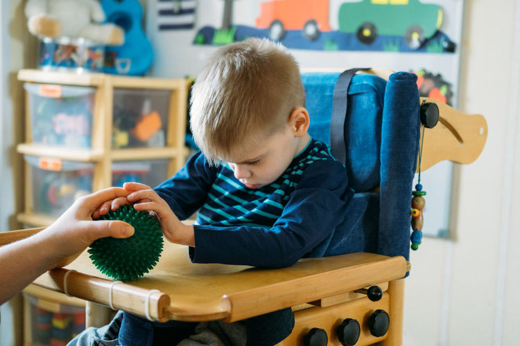 Boy holding toy sitting at home