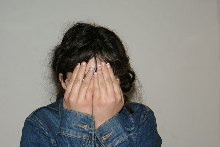 A girl in a blue denim jacket covers her face with her hands. Blue Jacket Close-up Denim Jacket Face Covered Front View Girl Gray Background Hiding Human Body Part Human Hand One Person Real People Shy Space For Copy Unidentifiable Person