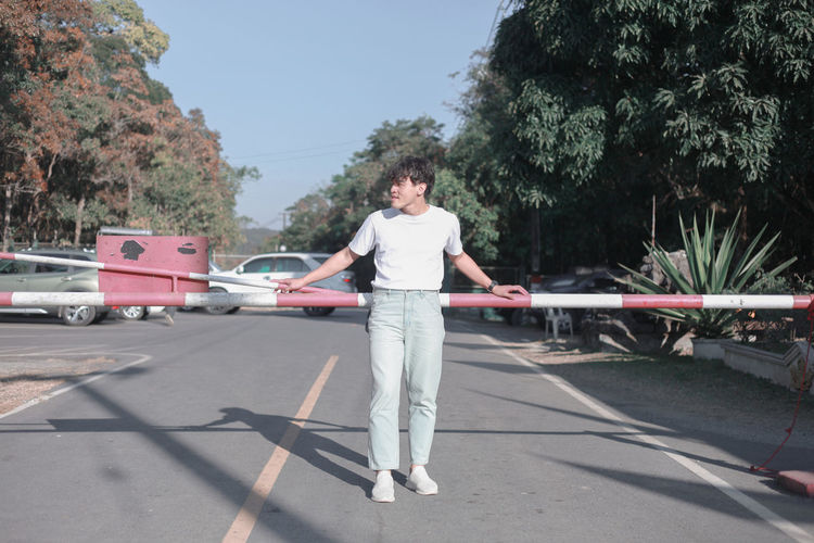 Man on road against trees