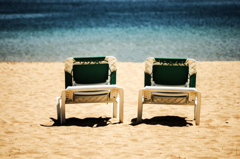 Empty lounge chairs at sandy beach