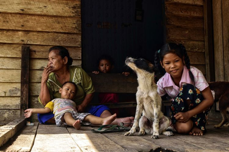 Grandmother With Grandchildren Sitting At Doorway