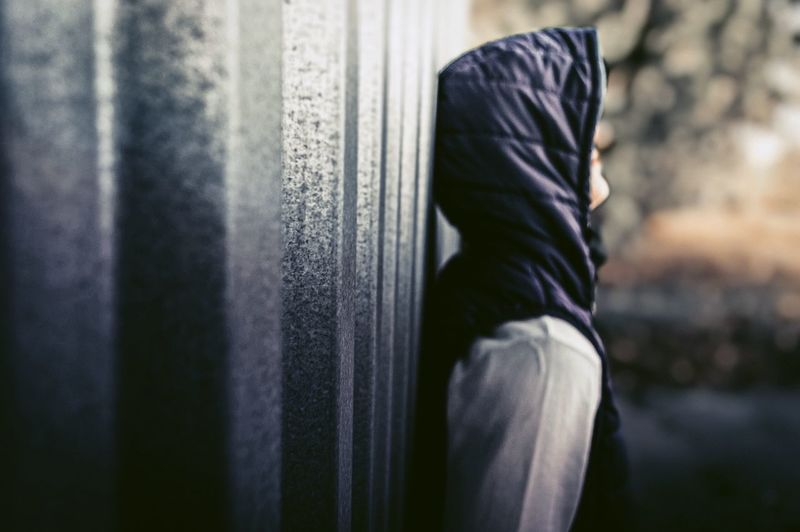 Side view of young man wearing hood standing by wall