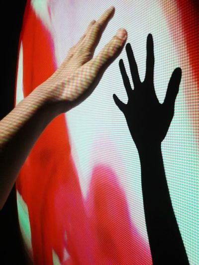 Cropped hand of person with shadow on projector