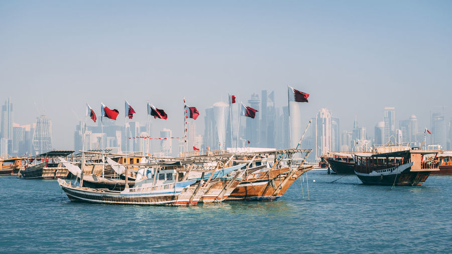 Doha Middle East Travel Architecture Building Exterior Built Structure City Day Dhow Flag Mode Of Transport Nature Nautical Vessel No People Outdoors Patriotism Qatar Sky Transportation Water Waterfront