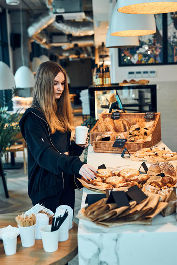Young woman standing by food at store
