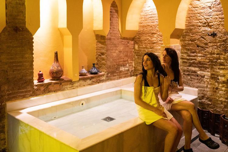 Women sitting by hot tub against wall