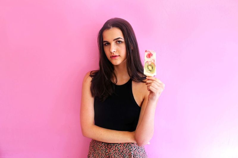 Portrait of young woman against pink background