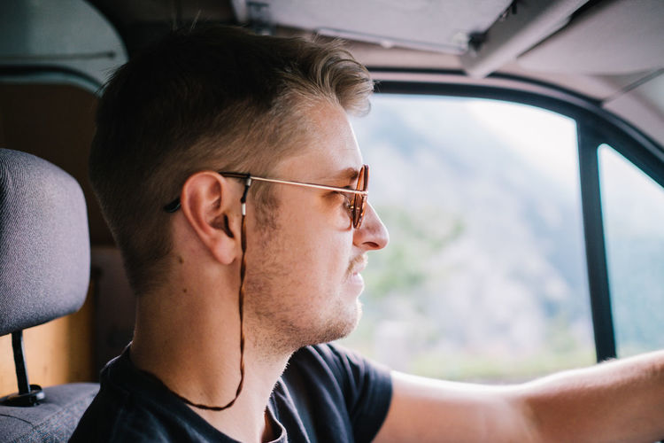 Profile view of young man wearing sunglasses while driving car