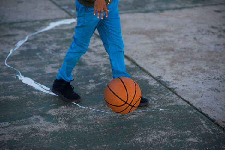 Low section of man playing basketball on footpath