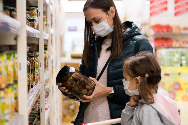 Mother and daughter wearing mask at supermarket