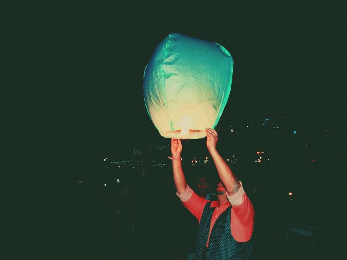 Man releasing pape0r lantern during night