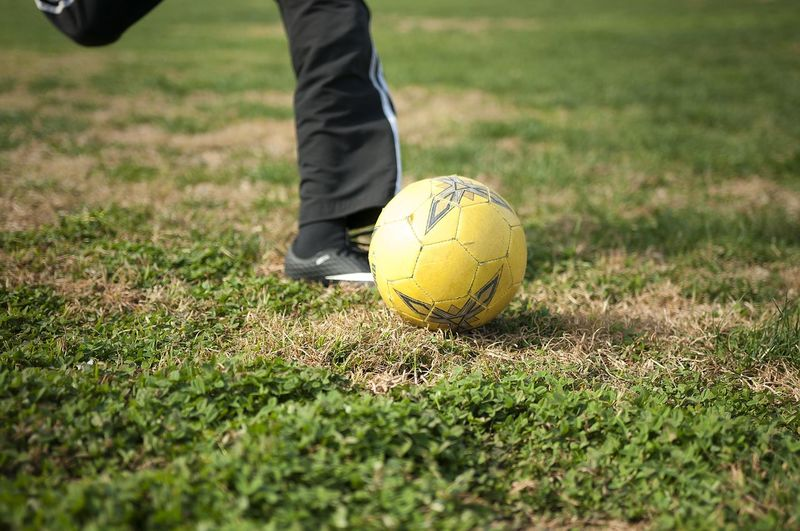 Low section of boy kicking ball while playing soccer on field
