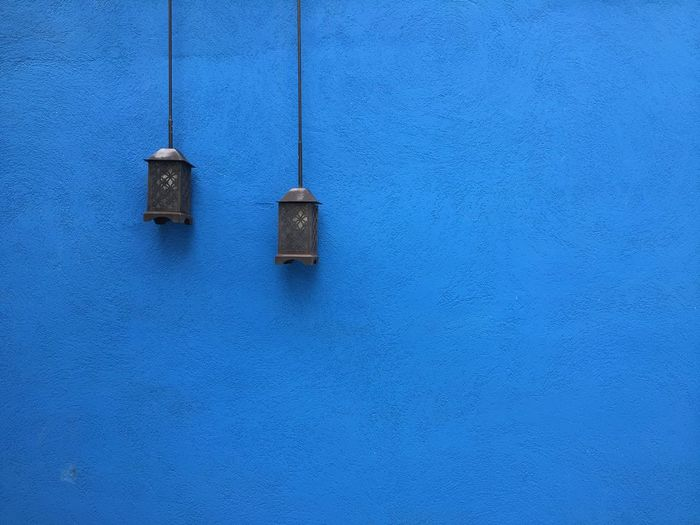 Lanterns hanging by blue wall