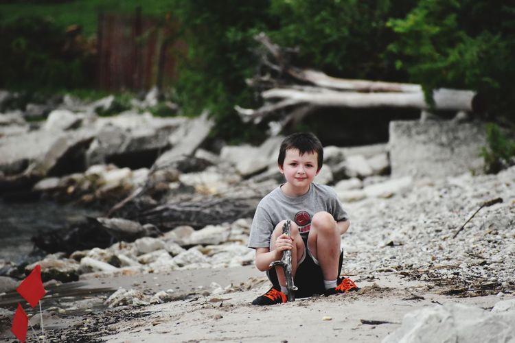 Portrait of boy sitting on land