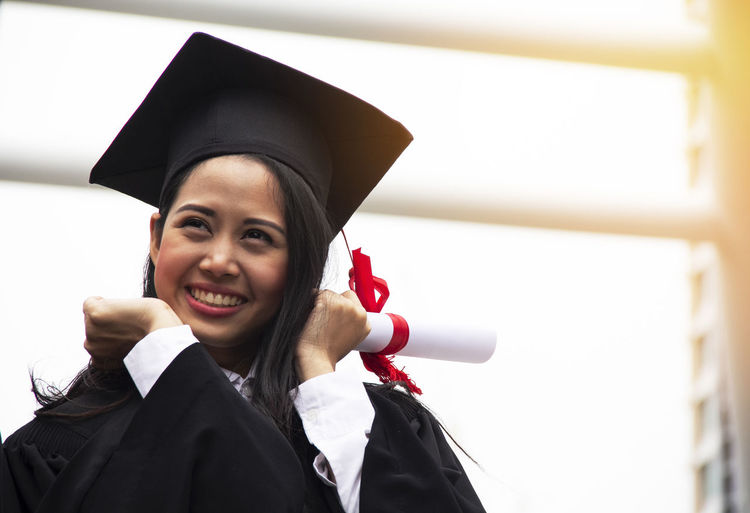 Achievement Beautiful Woman Cheerful Education Emotion Graduation Graduation Gown Happiness Headshot Learning Looking At Camera Mortarboard Outdoors Portrait Smiling Student Success University University Student Women Young Adult Young Women