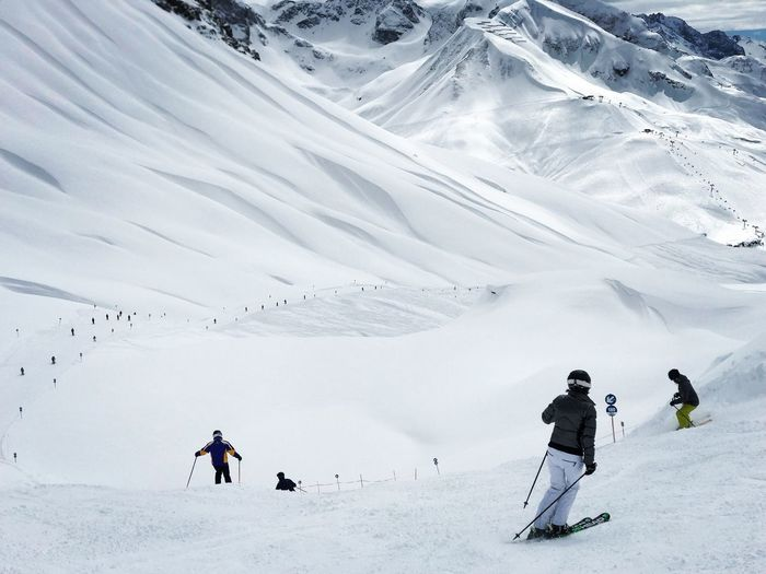 People skiing on snowcapped mountain in lech