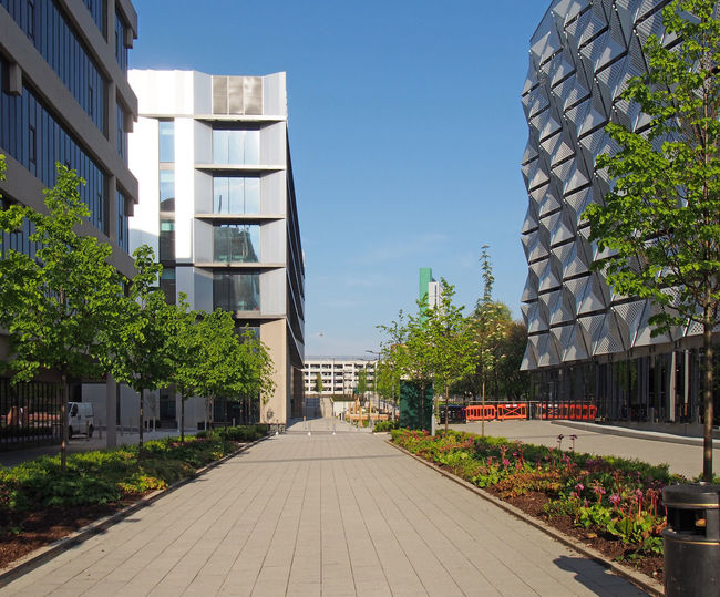 Footpath amidst buildings against sky in city