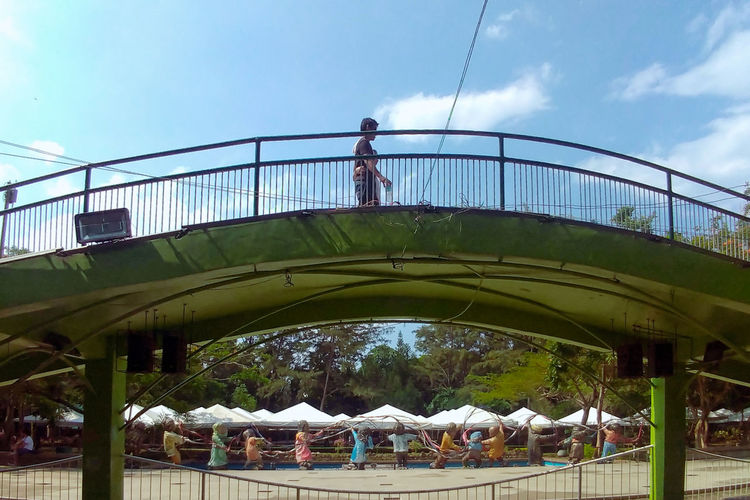 Low angle view of people standing on bridge against sky