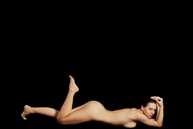 Portrait of sensuous woman lying down against black background