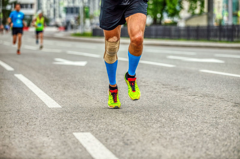 Legs runner man in compression socks and knee pads run race down street