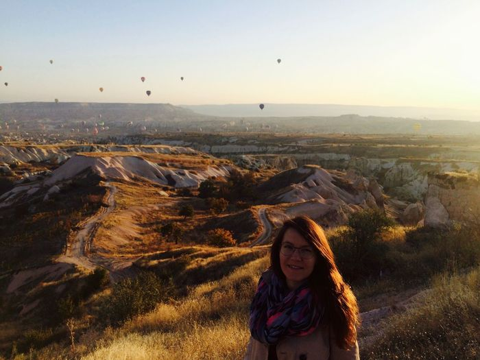 Portrait of smiling woman standing on rock formation at cappadocia