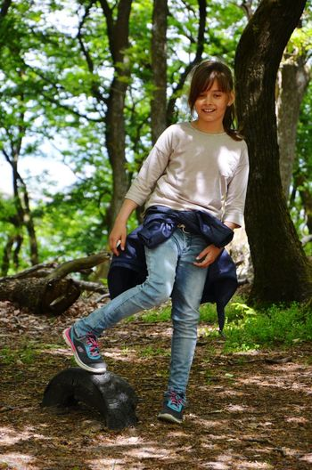 Portrait of smiling young woman playing in forest