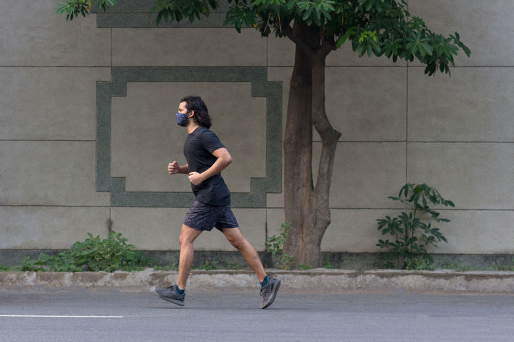 Side view of a man wearing a mask jogging on the road.