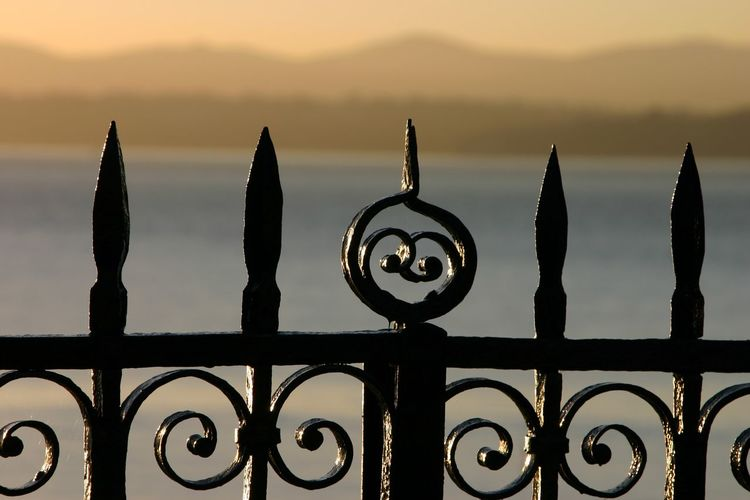 Close-up of metal fence against sky during sunset