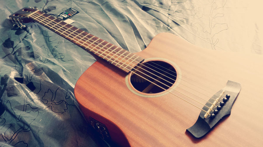 Close-up Of Guitar On Bed