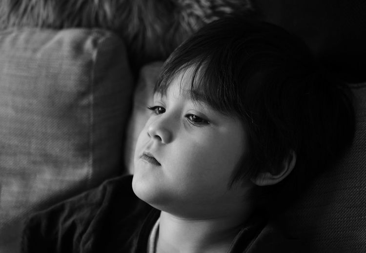 Close-up of boy leaning on sofa