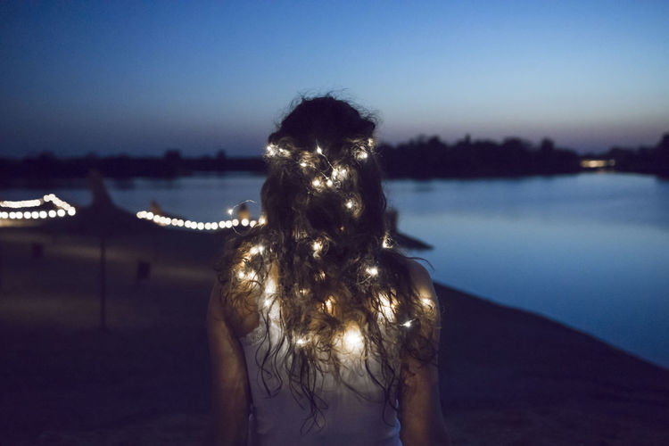 Rear View Of Woman With Illuminated String Lights Standing At Beach Against Sky