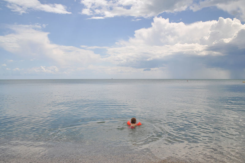 Child swimming in sea against cloudy sky
