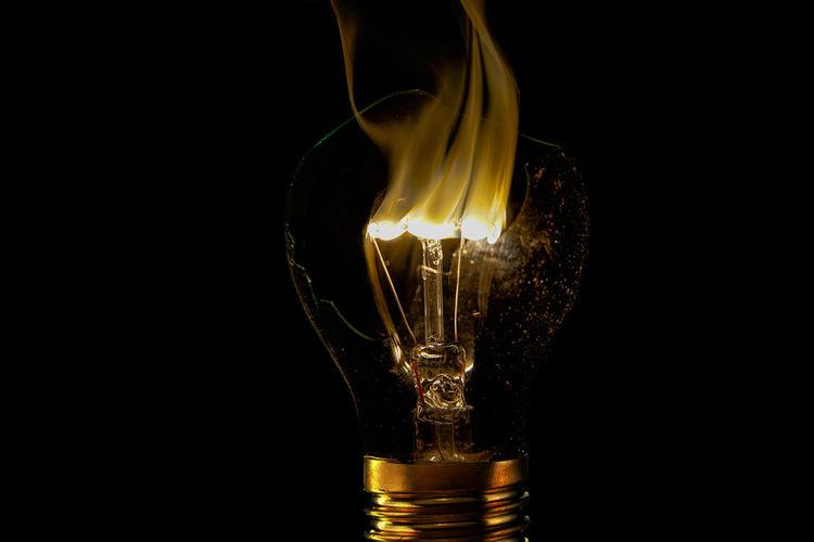 Close-up of illuminated light bulb against black background